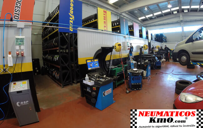 Interior de taller mecánico. Almacén con estanterías de neumáticos al aire libre y maquinaria tecnológica en primer plano