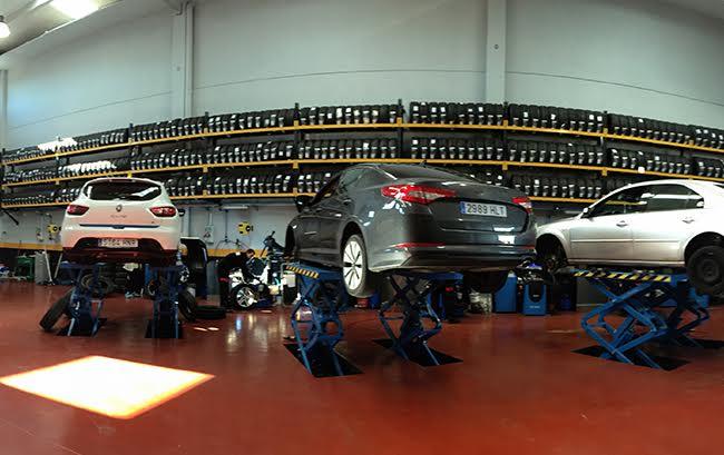 Fotografía interior taller mecánico. Fondo pared con expositor de neumáticos