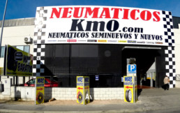 Fotografía frontal exterior taller km0 con cartel publicitario