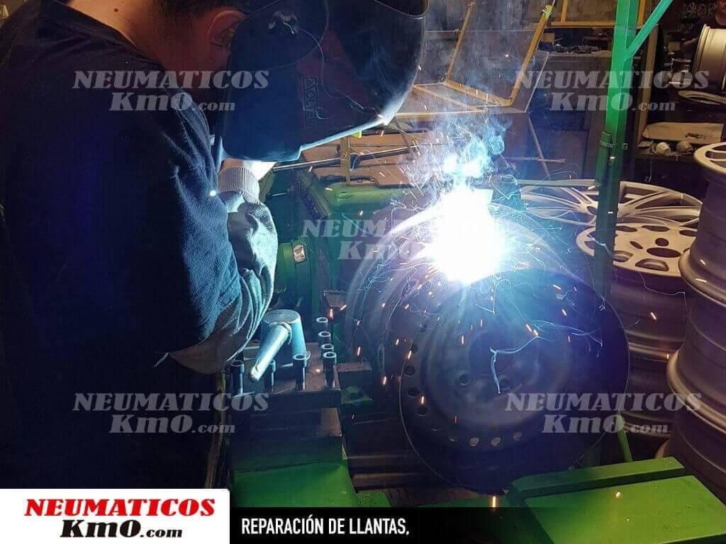 Reparación de llantas. Fotografía de operario efectuando Soldadura de llantas en torno