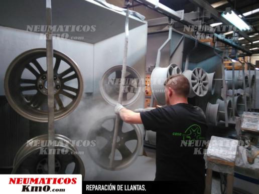 Reparación de llantas. Fotografía de un mecánico pintado llantas en polvo