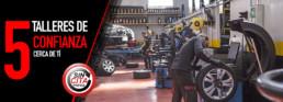 Fotografía interior de un taller con varios mecánicos trabajando. 5 talleres de confianza cerca de ti. Sin cita previa