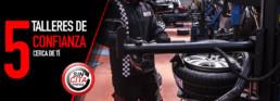 Fotografía tres cuartos de un mecánico manipulando un neumático. 5 talleres de confianza cerca de ti. sin cita previa