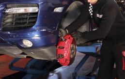 Trabajador realizando cambio de pastillas y discos de freno a un vehículo