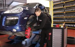 Trabajador realizando el cambio de pastillas y disco de freno de un vehículo al interior del taller
