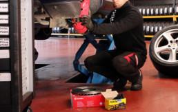 Trabajador en labores de cambio de pastillas de freno a un vehículo