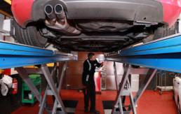 Trabajador de la empresa revisando la parte baja de un vehículo
