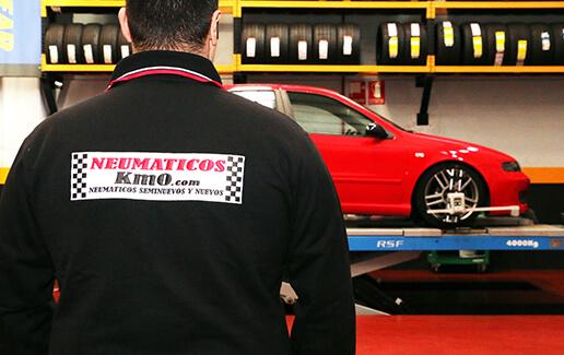 Fotografía interior de taller mecánico con trabajador y vehículo en proceso de paralelo y equilibrado de ruedas