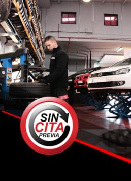 Fotografía interior de taller mecánico con trabajador manipulando neumáticos nuevos