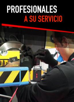 Fotografía de un técnico trabajando en el taller mecánico con cartel superior que reza Profesionales a su servicio