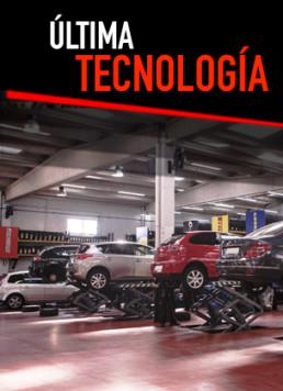 Fotografía del interior de un taller de Neumáticos Km0 con 5 vehículos en mantenimiento y rótulo superior central con la frase última tecnología